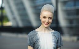 Ritratto della ragazza sorridente dei pantaloni a vita bassa con mohawk biondo dietro i precedenti all'aperto urbani della città Fotografie Stock Libere da Diritti