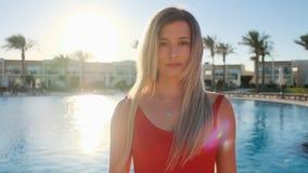 Ritratto della ragazza sorridente, esaminante macchina fotografica Bella donna in costume da bagno rosso vicino alla piscina blu  stock footage