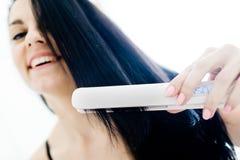 Ritratto della ragazza sorridente a letto con i capelli neri diritti facendo uso del raddrizzatore immagine stock