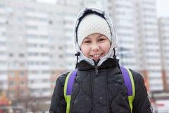Ritratto della ragazza sorridente preteen graziosa in vestiti di inverno, rivestimento gonfio con il cappello della lana e cappuc fotografie stock