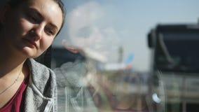 Ritratto della ragazza stanca e triste che si siede vicino alla finestra e che aspetta il suo aeroplano in terminale dell'aeropor video d archivio