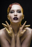 Ritratto della ragazza su un fondo nero con le armi tinto da oro Immagini Stock Libere da Diritti