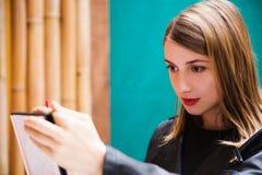 Ritratto della ragazza sveglia che mette rossetto rosso Fotografia Stock Libera da Diritti