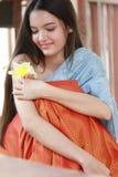 Ritratto della ragazza sveglia che odora il fiore in sua mano fotografia stock