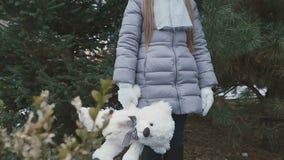 Ritratto della ragazza sveglia con l'orso ai precedenti dell'abete stock footage