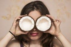 Ritratto della ragazza sveglia con le noci di cocco in vicino lei occhi immagine stock
