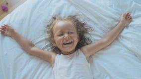 Ritratto della ragazza sveglia del bambino che si trova sul letto, esaminando macchina fotografica e risata video d archivio