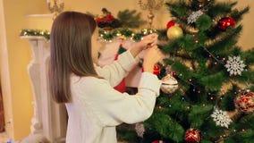 Ritratto della ragazza sveglia in maglione che decora l'albero di Natale con le bagattelle video d archivio