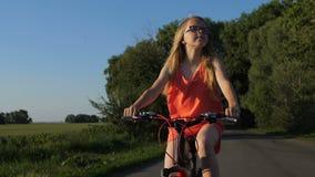 Ritratto della ragazza teenager su una bicicletta in campagna archivi video