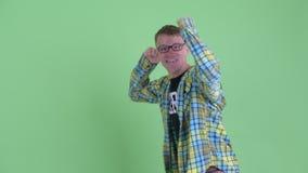 Ritratto della rappresentazione felice dell'uomo del nerd da appoggiare e sembrare sorpresa stock footage