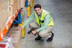 Ritratto della scatola sorridente di esame del lavoratore del magazzino fotografia stock libera da diritti