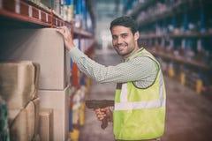 Ritratto della scatola sorridente di esame del lavoratore del magazzino fotografie stock