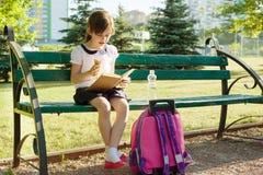 Ritratto della scolara 7 anni su un libro di lettura del banco, mangiante il gelato Cortile della scuola del fondo Immagini Stock Libere da Diritti