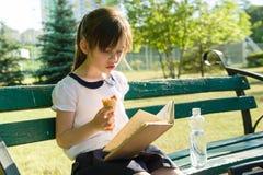 Ritratto della scolara 7 anni su un libro di lettura del banco, mangiante il gelato Parco della città del fondo Immagine Stock Libera da Diritti