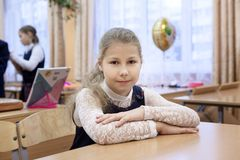 Ritratto della scolara caucasica che si siede allo scrittorio in aula e che esamina macchina fotografica Fotografia Stock