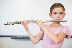 Ritratto della scolara che gioca flauto in aula Immagini Stock