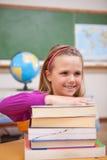 Ritratto della scolara che posa con una pila di libri Fotografia Stock