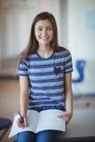 Ritratto della scolara che si siede sul banco e che scrive sul libro nell'aula Fotografia Stock Libera da Diritti