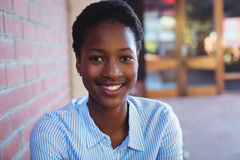 Ritratto della scolara felice che si siede accanto al muro di mattoni Fotografie Stock Libere da Diritti