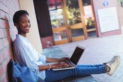 Ritratto della scolara felice che si siede contro il muro di mattoni e che per mezzo del computer portatile Immagine Stock