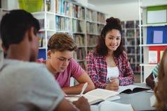 Ritratto della scolara felice che studia con i suoi compagni di classe in biblioteca Fotografie Stock