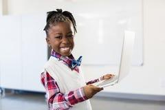 Ritratto della scolara felice che utilizza computer portatile nell'aula Fotografia Stock Libera da Diritti