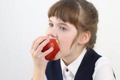 Ritratto della scolara graziosa in uniforme che mangia mela rossa Immagine Stock