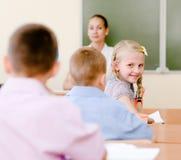 Ritratto della scolara nel luogo di lavoro con l'insegnante su fondo Immagini Stock