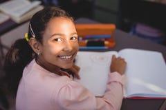 Ritratto della scolara sorridente che fa il suo compito in biblioteca Immagini Stock Libere da Diritti