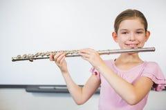 Ritratto della scolara sorridente che gioca flauto in aula Fotografie Stock