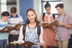 Ritratto della scolara sorridente che sta con il libro in aula Fotografie Stock