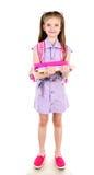 Ritratto della scolara sorridente con i libri e lo zaino isolati Fotografia Stock