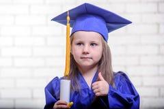 Ritratto della scolara sveglia con il cappello di graduazione in aula Immagini Stock Libere da Diritti