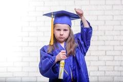 Ritratto della scolara sveglia con il cappello di graduazione in aula Immagine Stock Libera da Diritti