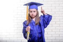 Ritratto della scolara sveglia con il cappello di graduazione in aula Fotografia Stock Libera da Diritti