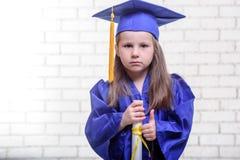 Ritratto della scolara sveglia con il cappello di graduazione in aula Fotografia Stock