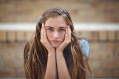 Ritratto della scolara triste che si siede da solo nella città universitaria Fotografie Stock Libere da Diritti