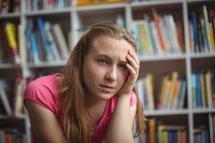 Ritratto della scolara triste che si siede nella biblioteca Fotografia Stock