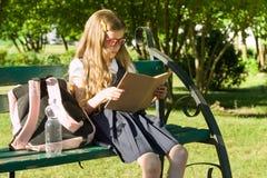 Ritratto della scuola primaria della scolara con lo zaino su un libro di lettura del banco, cortile della scuola del fondo Fotografia Stock