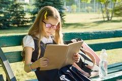 Ritratto della scuola primaria della scolara con lo zaino su un libro di lettura del banco, cortile della scuola del fondo Fotografia Stock Libera da Diritti