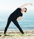 Ritratto della sportiva che sta praticando l'allungamento nel nero Fotografie Stock Libere da Diritti