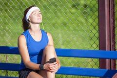Ritratto della sportiva nel rilassamento dell'attrezzatura di sport di estate all'aperto immagini stock