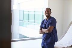 Ritratto della stanza maschio dell'esame di Wearing Scrubs In dell'infermiere immagini stock libere da diritti