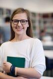 Ritratto della studentessa in biblioteca Immagine Stock