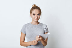 Ritratto della studentessa con il panino leggero dei capelli, vestito con indifferenza, tenendo taccuino in mani, andanti scriver Immagini Stock Libere da Diritti