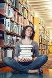 Ritratto della studentessa matura di medio evo stanco che si siede nella biblioteca con gli occhi chiusi che meditano, addormenta Fotografie Stock Libere da Diritti