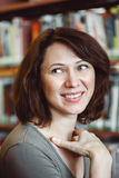 Ritratto della studentessa matura sorridente di medio evo in biblioteca che distoglie lo sguardo, professione del primo piano del Fotografie Stock