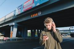 Ritratto della via di un giovane che scrive un messaggio su uno smartphone ed ascolta musica Un giovane sta aspettando il transp  Immagini Stock Libere da Diritti