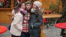 Ritratto delle amiche di risata divertendosi sul mercato di Natale Gli amici felici passa insieme il tempo durante archivi video