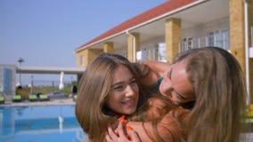 Ritratto delle amiche felici, abbraccio emozionale di bei migliori amici vicino allo stagno blu durante le vacanze estive a video d archivio